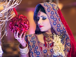 Indian Wedding bride in red diamonds sari saree holding gorgeous red flowers at Richardson Renaissance Hotel in Texas