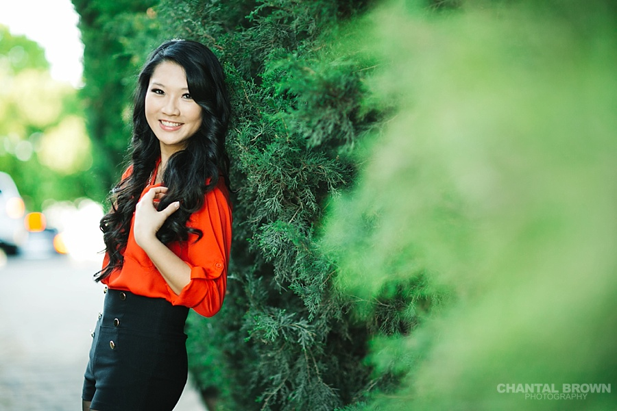 Best backlit sunset senior portraits McKinney TX leaning next to beautiful tall pine green pine trees at Adriatica Village by Chantal Brown.