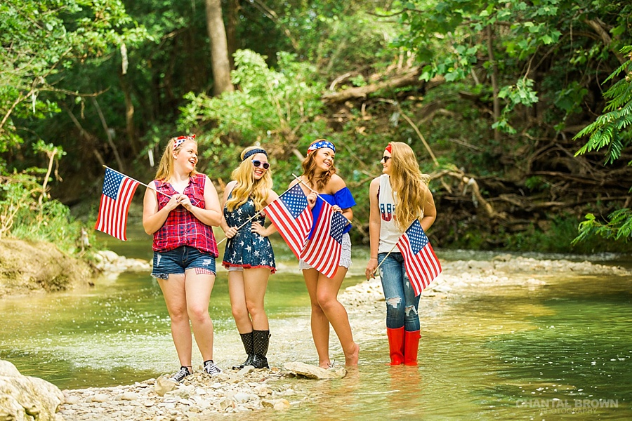 4th of July styled senior portraits in Dallas by the water creek river happily holding American flags.
