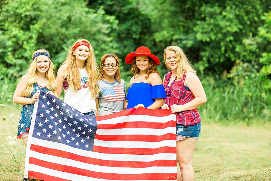 The gorgeous 4th of July styled senior portraits group session taken by the best Chantal Brown photography in Dallas holding a big American flag with her senior models.