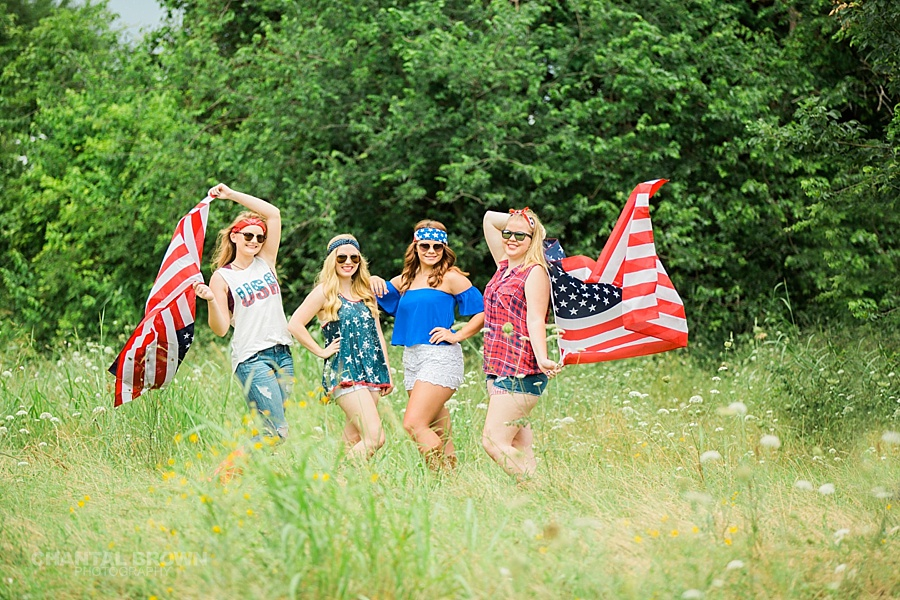 4th of July styled senior portraits for red white and blue American flag standing in tall grass field taken by Chantal Brown Photography.