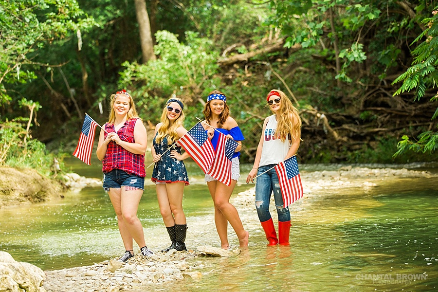 4th of July theed senior portraits group photo shoot in Dallas by the water creek river holding American flags.