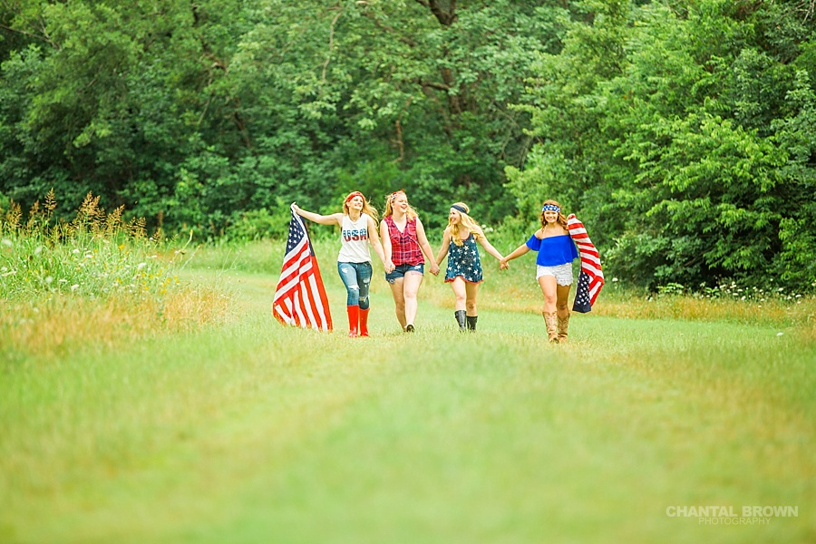 The best American flag styled senior portraits in Dallas walking in grass field.