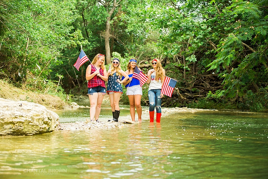 American flag styled senior portraits group session in Dallas by the water creek river holding.