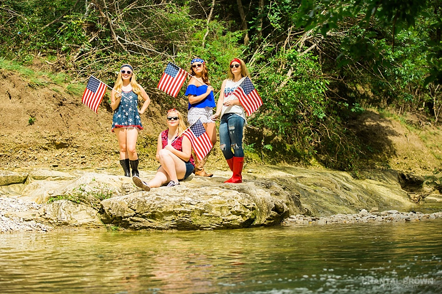 Happy 4th of July Dallas senior portraits taken by the water creek river the girls are holding American flags.