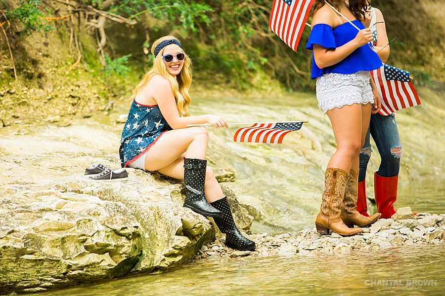 Happy 4th of July themed senior porgraits group photo shoot in Dallas relaxing by the water river creek, holding an American flag.