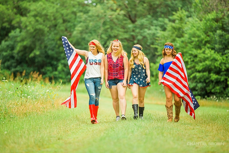 Independence Day styled senior portraits group photo shoot in Dallas walking in grass field holding American flags.