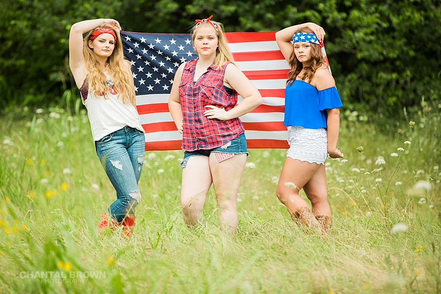 July 4th senior model group session in Dallas holding an American flag in a tall grass field taken by Chantal Brown Photography.