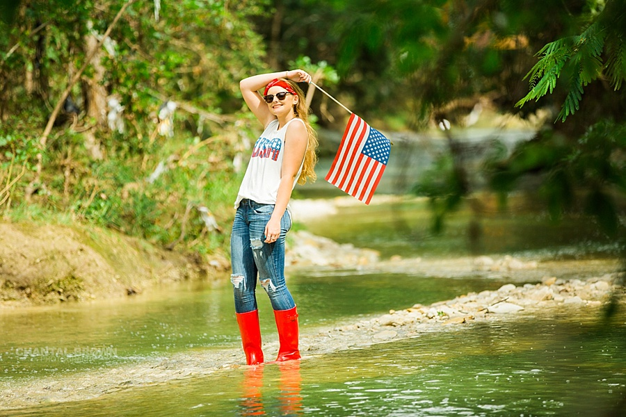 4th of July senior portraits holding American Flag taken in Dallas water creek river for a Plano high school student. She