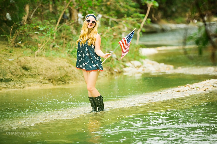 All American high school student senior portraits holding a small American flag taken in Dallas water creek river by Chantal Brown photography.