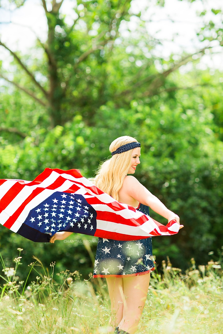 Holding the real American flag outdoor. All American high school by Chantal Brown Photography.