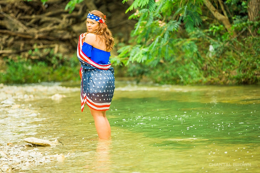 Wrapped around American flag scarf creative senior portraits photo shoot taken in Dallas water creek river with gorgeous red white and blue outfit.