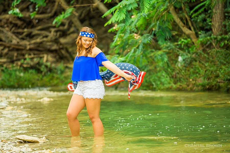 Holding American flag scarf inspiration senior portraits session taken in Dallas water creek river wearing very cute outfit.