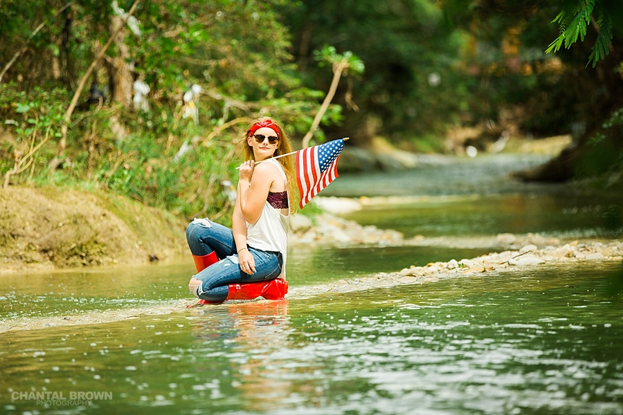 All American flag senior portraits of a Plano high school student taken in Dallas. The senior girl standing in the water creek river wearing pretty outfit.