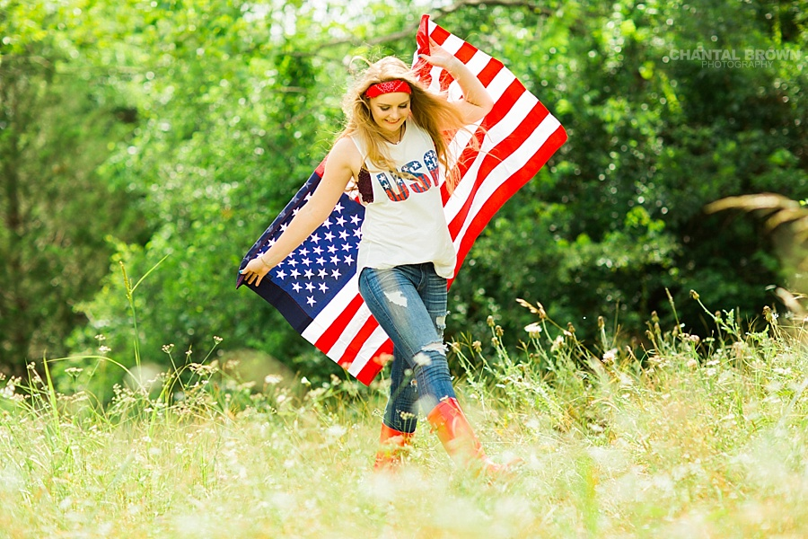 American flag senior portraits taken in Dallas of a Plano high school senior student. It was taken outdoor in a tall grass field wearing all American outfit. www.chantalbrownphotography.com