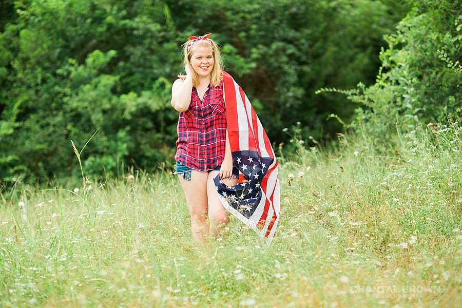 Creative senior portraits photo shoot taken outdoor holding an American flag at the park with tall grass field. Taken by Dallas Chantal Brown Photography.