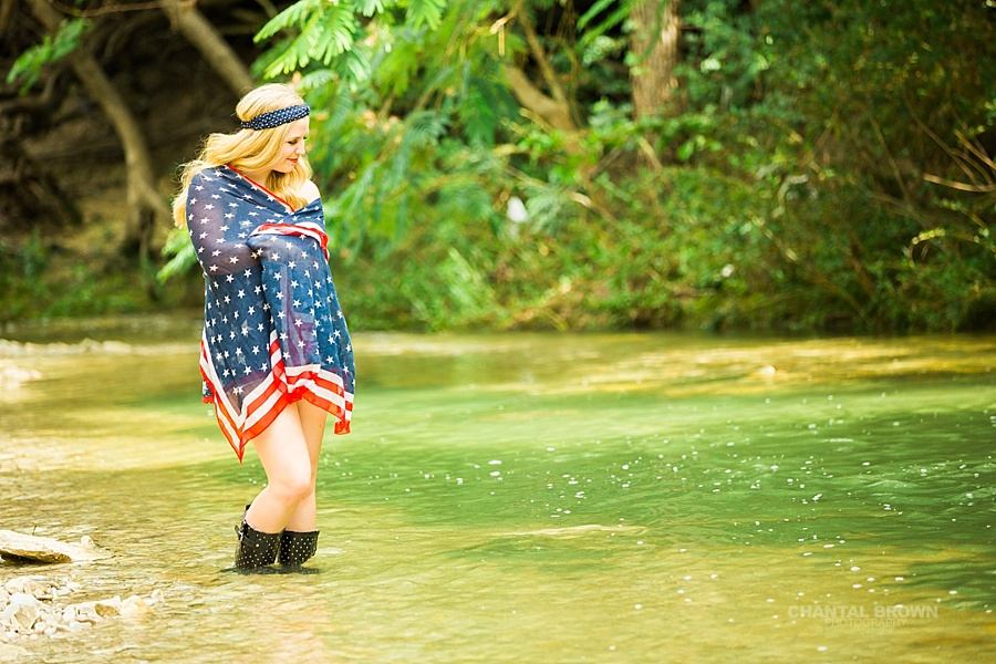 Creative senior portraits of an Allen high school senior student wrapped around American flag scarf standing in the water creek river.