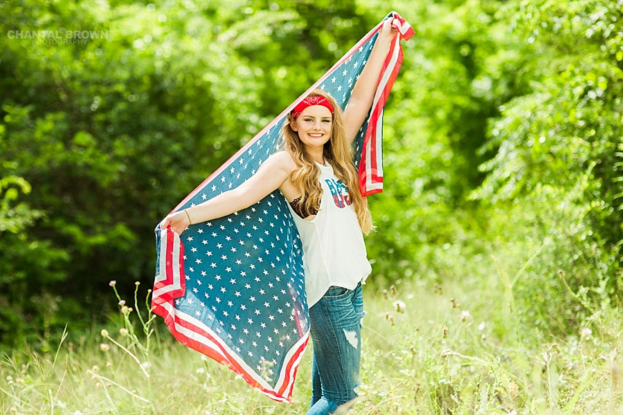 Dallas senior portraits holding an American flag scarf outdoor at a tall grass field during high noon in Dallas for a Plano East High girl. www.chantalbrownphotography.com