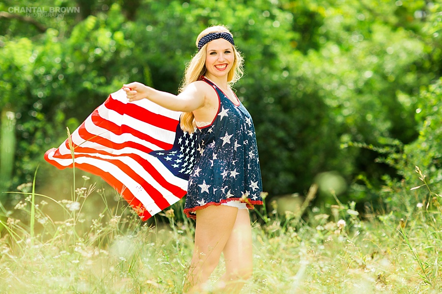 Dallas senior portraits of an Allen high school student holding and flying American flag, wearing gorgeous outfit outside a park in tall grass field. Taken by Dallas Chantal Brown Photography.