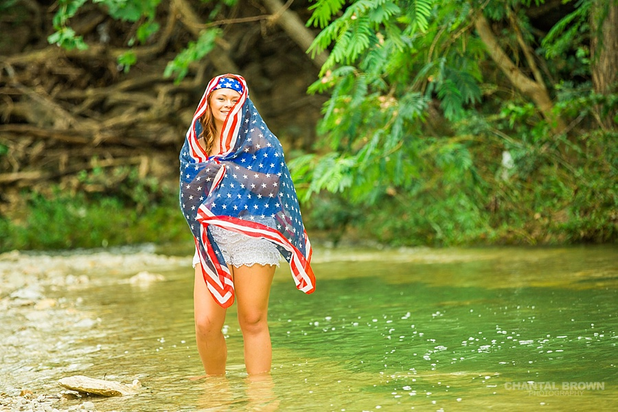 Laughing and having fun with Dallas senior portraits photographer of a Mesquite high school student wrapped around American flag scarf and standing in the water creek river.