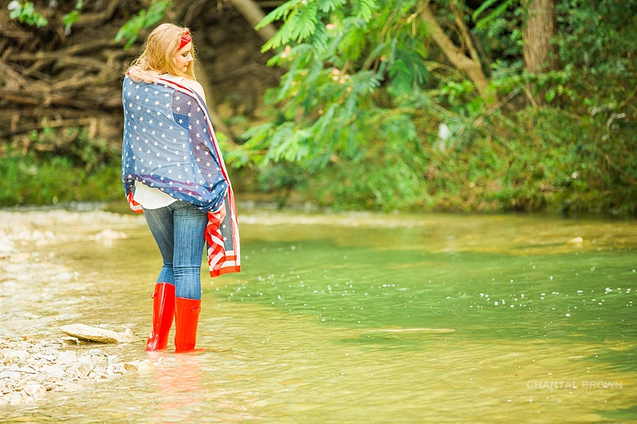 Happy 4th of July of Plano East high school student wrapped around an American flag scarf Dallas senior portraits standing in the Water River Creek. Also wearing very cute red, white and blue boots.