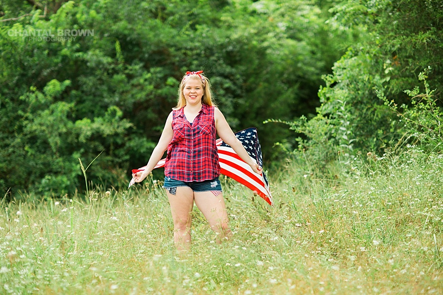 Happy 4th of July holding an American flag scarf standing in the tall grass field. Taken in Dallas outdoor for Carrollton high school senior student.