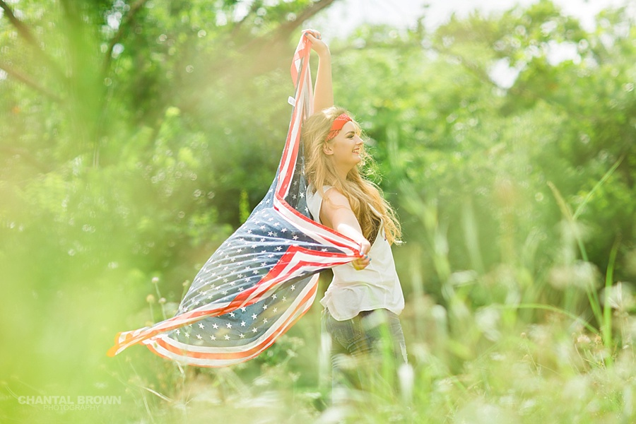 Happy Independence Day senior portraits holding an American flag scarf in Dallas grass field.