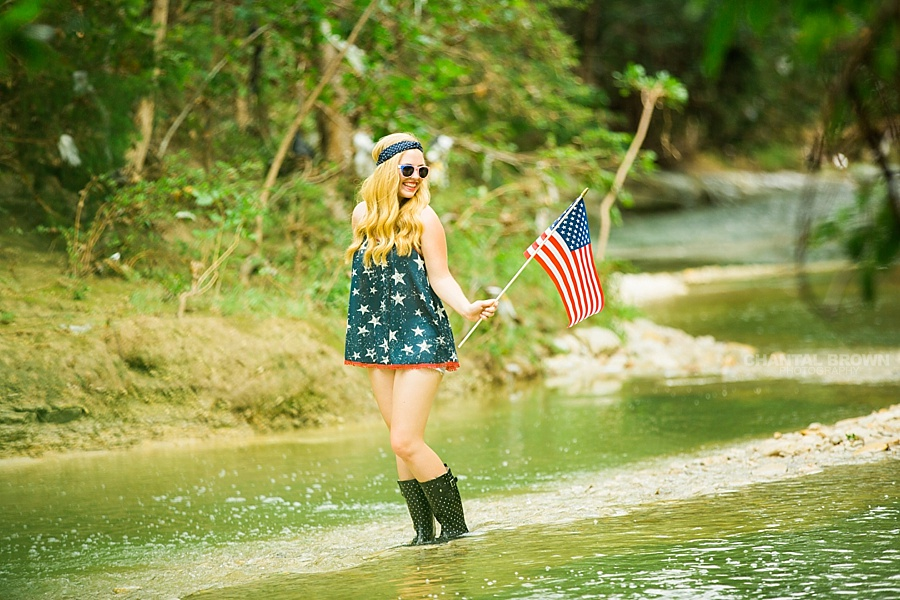 Independence Day celebration holding a small American flag senior portraits taken outdoor in Dallas in the water river creek.