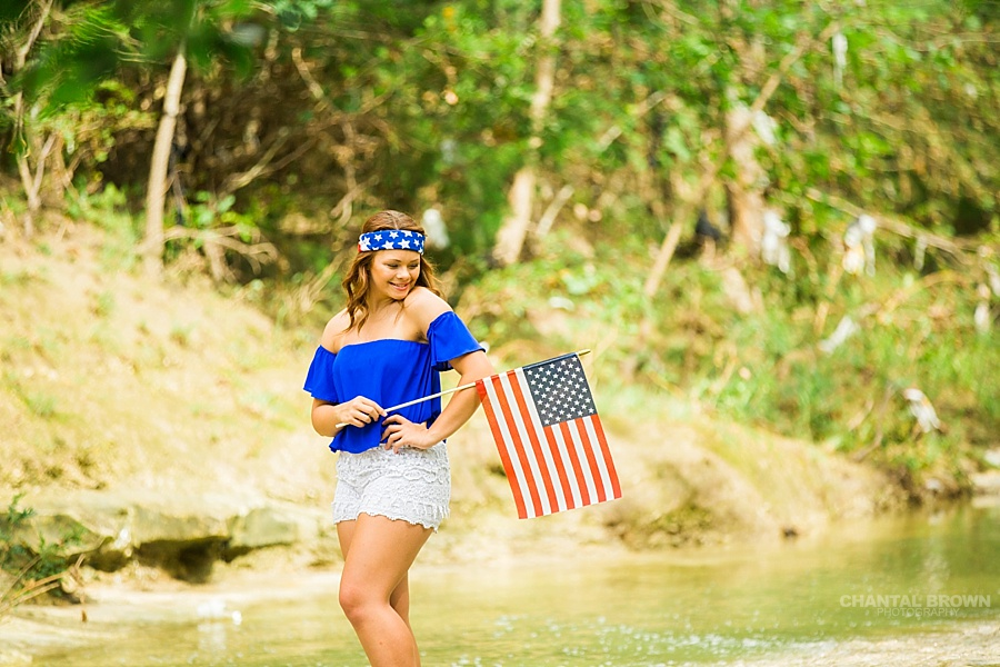 Very cute patriotic clothes of an All American girl holding flag and standing in the water creek river. Taken by Dallas Chantal Brown Photography. www.chantalbrownphotography.com