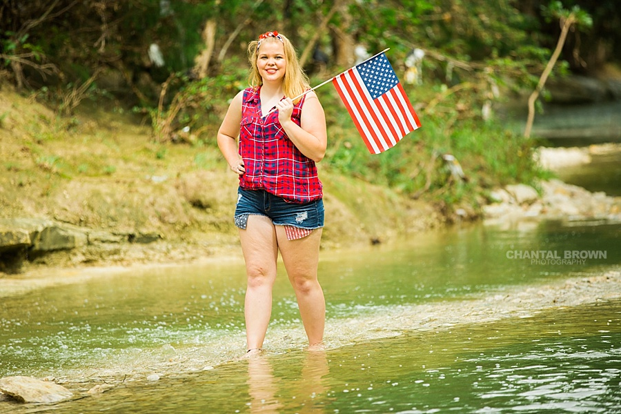 Very adorable red white and blue clothes. Wearing very patriotic summer outfit styled Dallas senior portraits standing in the water and holding an American flag outfit. www.chantalbrownphotography.com
