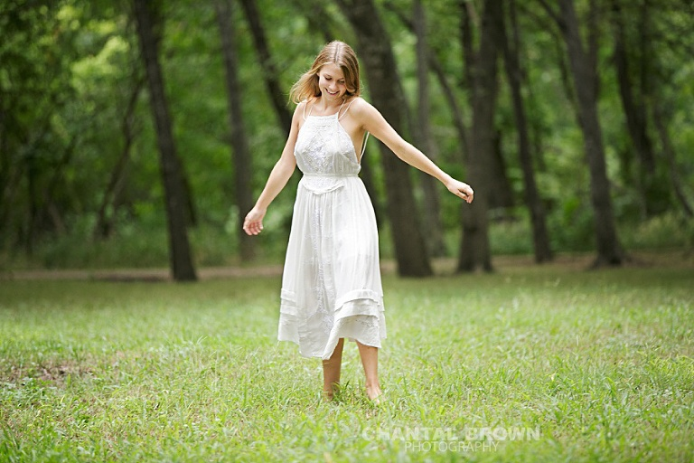 Plano high school senior photographer spinning a white dress in the field by Chantal Brown Photography.