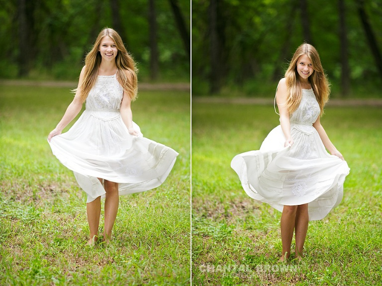 Plano senior picture spinning around in a white dress in the green grass field by Chantal Brown Photography.