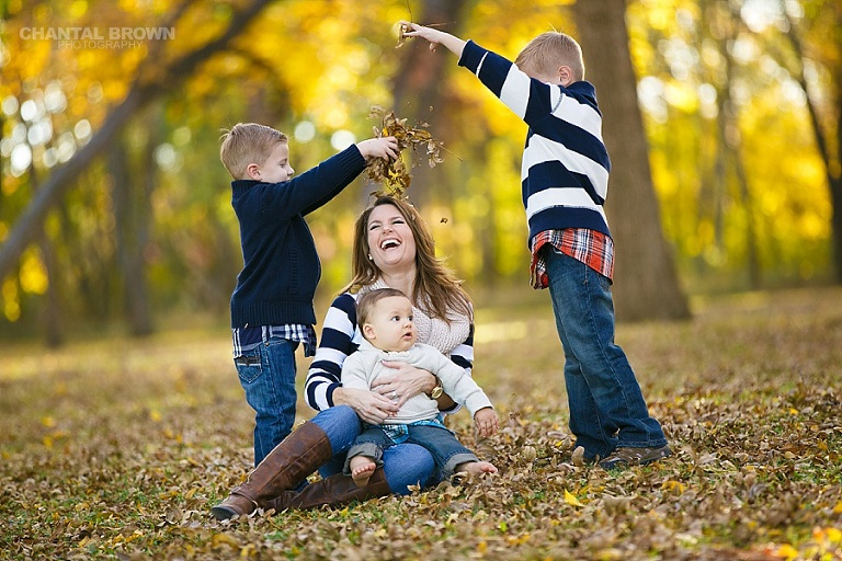 kids and mom laughing while playing in the fall yellow leaves family portrait in Plano TX taken by Chantal Brown Photography