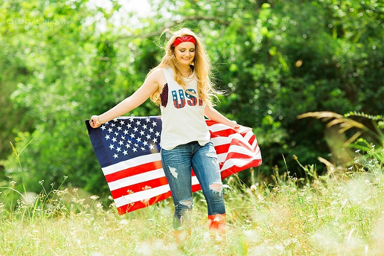 American flag senior portraits taken in Dallas walking in a tall grass field in high noon. By Dallas Chantal Brown Photography.